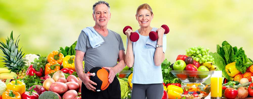 Healthy senior couple exercising over fresh fruits and vegetables background advocating to eat and stay healthy and maintain strong bones through calcium and vitamin d