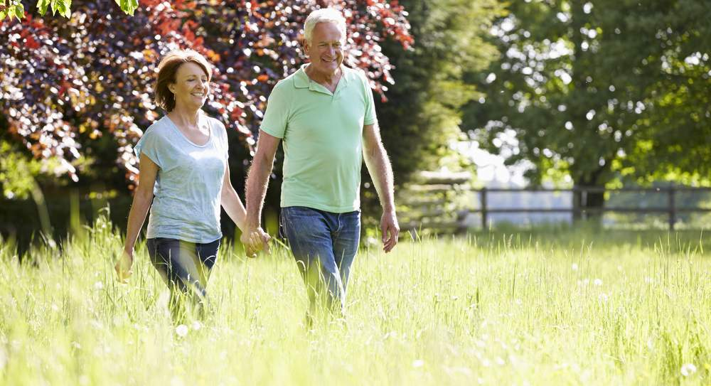 happy couple enjoying the outdoors and walking through a large grass lawn getting exercise